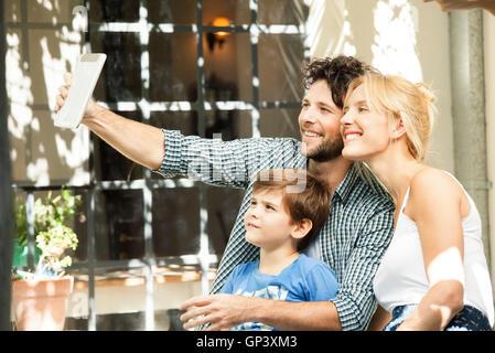 Familie mit einem Kind posiert für Selfie mit digital-Tablette genommen - Stockfoto