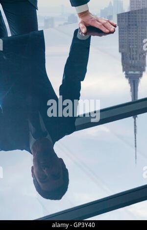 Geschäftsmann Reflexion in Glasplatte Tisch gelehnt - Stockfoto