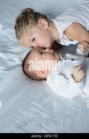 Kleines Mädchen mit kleinen Bruder kuscheln - Stockfoto