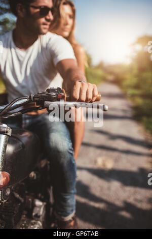 Aufnahme des jungen Paares auf dem Motorrad abgeschnitten. Mann reitet auf einem Motorrad mit Freundin an einem - Stockfoto