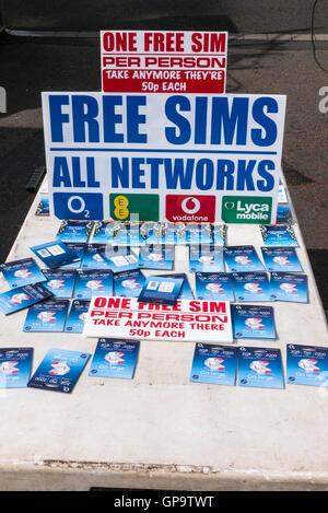 Kostenlose SIM-Karten für Mobiltelefone auf einem Marktstand mit Schild beraten Menschen, eine pro Person, inklusive - Stockfoto