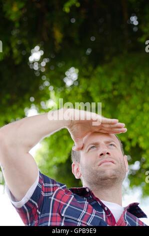 Verlässt der Mann Blick auf seine Zukunft mit seiner Hand über die Augen im Freien mit Grün im Hintergrund. - Stockfoto