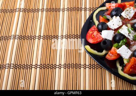 Frische vegetarische Salat aus Tomaten, Gurken, Zwiebeln, Oliven, Paprika und Feta-Käse in einer schwarzen Platte - Stockfoto