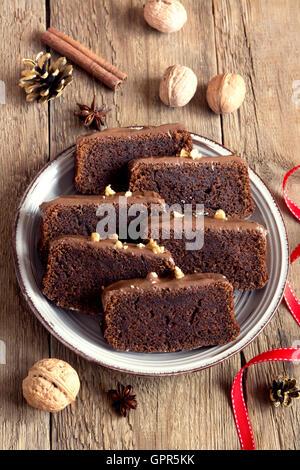 In Scheiben geschnittene Schokoladenkuchen mit Nüssen und Gewürzen zu Weihnachten über rustikale Holz Hintergrund - Stockfoto