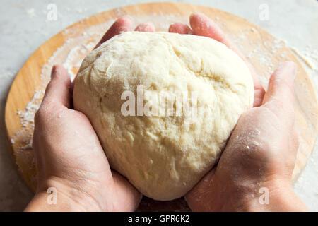 Rohe hausgemachte Pizzateig auf Schneidebrett mit Händen - Stockfoto