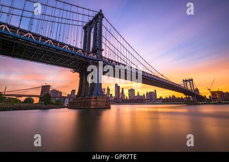 New York City an der Manhattan Bridge über den East River während des Sonnenuntergangs. - Stockfoto