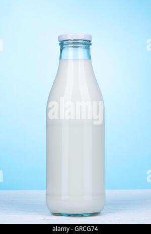 Milchflasche weiße Holzbrett und hellblauen Hintergrund - Stockfoto