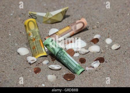 Geld, Banknoten, Münzen und Muscheln im Sand, als Symbol für Urlaub und Urlaubsgeld - Stockfoto