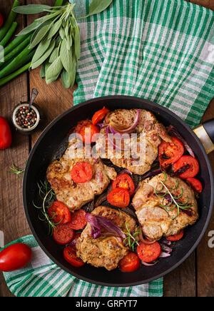 Saftiges Schweinesteak mit Rosmarin und Tomaten auf Pfanne. Ansicht von oben - Stockfoto