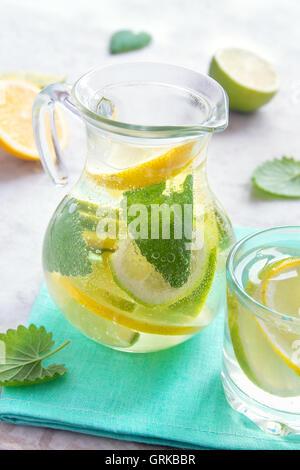Entgiftung mit Limone, Zitrone und Minze im Glaskrug Wasser (Limonade) - Stockfoto