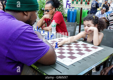 Manhattan New York City NYC NY Midtown Bryant Park Volkspark Spiele Schach Spielbrett schwarzen Mann Frau Mädchen - Stockfoto