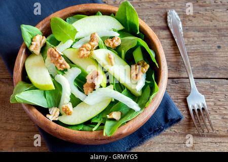 Waldorf-Salat mit grünem Apfel, Sellerie und Walnüsse in Holzschale über rustikale Hintergrund - Stockfoto