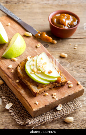 Erdnussbutter-Sandwiches mit Apfel auf rustikalen hölzernen Hintergrund - Stockfoto