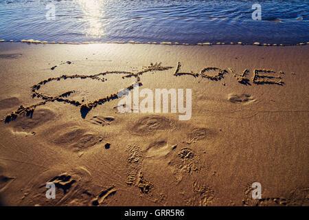 Herz und Pfeil gezeichnet auf dem Sand am Strand.  Liebe-Konzept - Stockfoto