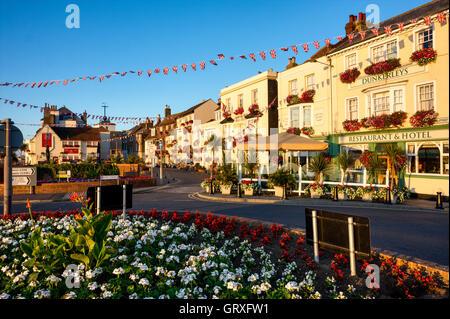 England, beschäftigen. Blumenschau am Kreisverkehr im Vordergrund, mit Beach Street Reihe mit drei Geschichte alte - Stockfoto