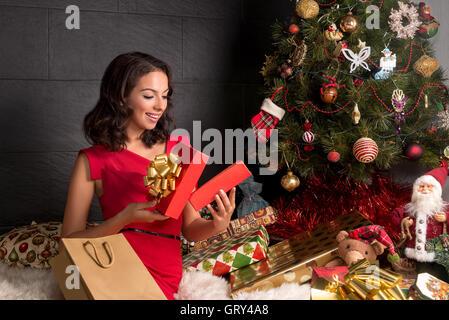 Frau öffnen Sie eine Geschenkverpackung. Weihnachtszeit. Xmas Tree - Stockfoto