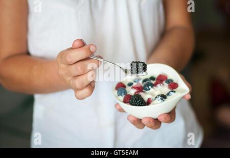 Das Mädchen bietet gesundes Frühstück Joghurt mit Beeren - Stockfoto
