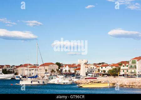Vodice, in der Nähe von Sibenik, Kroatien. Boote im Hafen festgemacht. Häuser, Palmen und Denkmal für die Opfer - Stockfoto