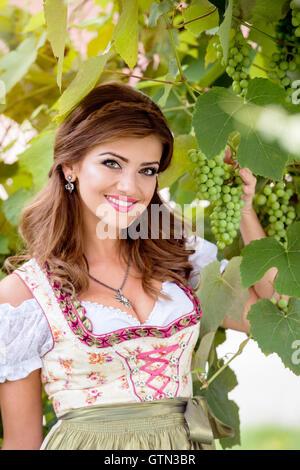 Schöne junge Frau in bayerischer Tracht halten grap - Stockfoto