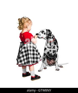 Kleine Mädchen gibt etwas Dalmatiner und er schnüffelt - Stockfoto
