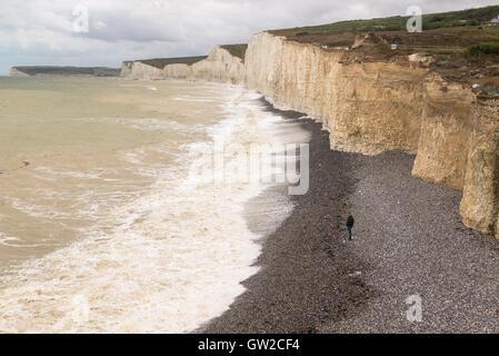 Solitary Man allein stehend auf einem Kiesstrand unterhalb der weißen Klippen von sieben Schwestern mit Blick auf - Stockfoto