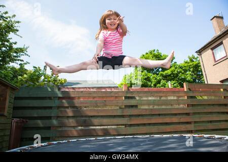 -MODELL VERÖFFENTLICHT. Junges Mädchen auf dem Trampolin. 8 Jahre altes Mädchen springen in der Luft während des - Stockfoto