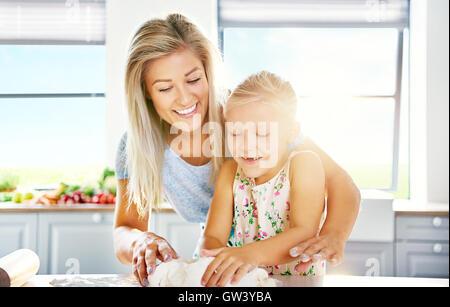 Mutter und Tochter Spaß in der Küche, wie das kleine Mädchen lernt bei kneten den Teig backen - Stockfoto