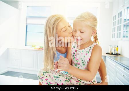 Schöne junge blonde Mutter küssen Tochter in Pferdeschwänze und Kleid, während Sie mit Brotteig spielt - Stockfoto