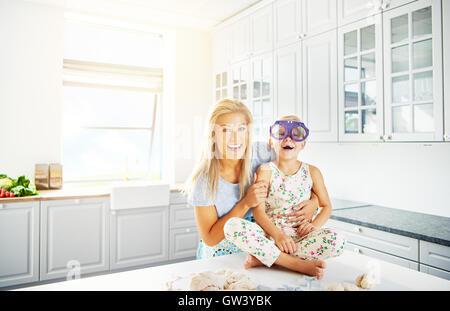 Helle Küche Szene mit Kopie von Frau lachendes Kind in Silly lila Brillen während auf Tisch - Stockfoto