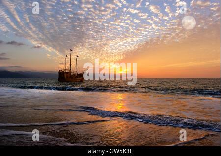 Piraten Schiff Fantasy ist eine alte hölzerne Piratenschiff mit voller Fahnen in einem farbenfrohen Sonnenuntergang - Stockfoto