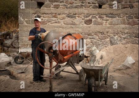 Albanischen Arbeiter mischt Zement auf Stellensuche Bau Reparatur einer Wand in Griechenland - Stockfoto