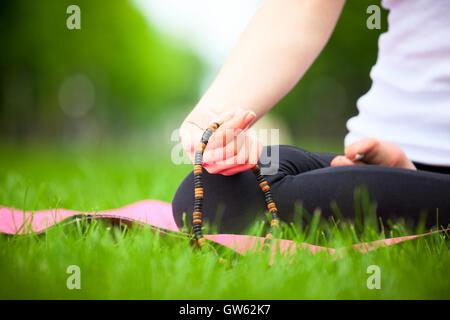 Nahaufnahme von weiblicher Hand, die Rosenkranz - Meditation-Konzept. - Stockfoto