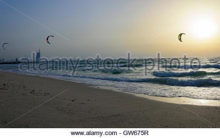 Kite-Surf in Dubai mit dem berühmten Burj Al Arab Hotel im Hintergrund. Aufnahme während eines Sonnenuntergangs. - Stockfoto