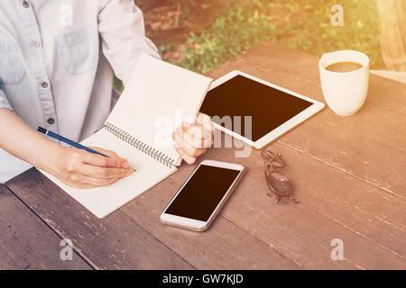 Frau Hand schreiben Notebook und Handy, tablet auf Tisch im Garten im Coffee Shop mit Vintage abgeschwächt. - Stockfoto
