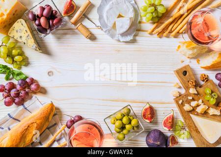 Verschiedene Arten von Käse, Wein und Snacks auf dem weißen Holz - Stockfoto