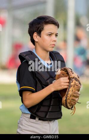Ein Teenager Baseball-Spieler tragen Catcher Getriebe bei einem Baseball-Spiel in Cairns, Australien - Stockfoto