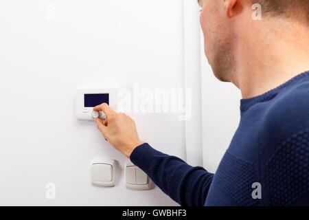 Mnner Regulieren Temperatur Am Bedienfeld Der Zentralheizung An Wand Im Wohnzimmer