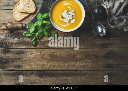 Kürbis Cremesuppe in Schüssel mit frischem Basilikum, Gewürze und gegrilltem Brot Scheiben über alten rustikalen - Stockfoto