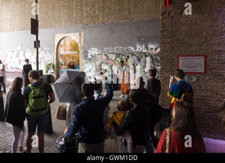 Ein paar Musiker als Straßenmusikant auf Clink Street, London, von einer Schar von Passanten beobachtet - Stockfoto