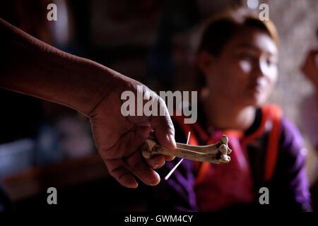 Ein Schamane hält einen Hühnerknochen fixiert durch Zahnstocher während eine traditionelle Praxis, um Krankheit - Stockfoto