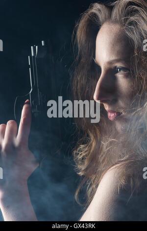 Frau mit einer Pistole im Dunkeln wegschauen - Stockfoto
