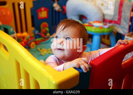 Babymädchen denken in einen bunten Laufstall - Stockfoto