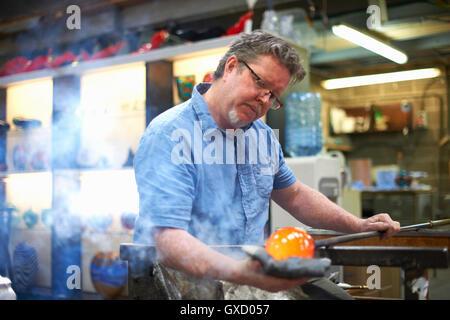 Glasbläser in Werkstatt bilden geschmolzenes Glas auf Blasrohr - Stockfoto