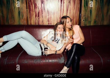 Zwei Erwachsene Freundinnen auf Sofa zurückgelehnt auf ausgehen in bar - Stockfoto