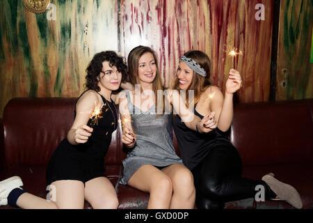 Drei Erwachsene Freundinnen spielen mit Wunderkerzen auf ausgehen in bar - Stockfoto