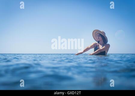 Junge Frau trägt Sonnenhut waten im tiefen Blau des Meeres, Villasimius, Sardinien, Italien - Stockfoto