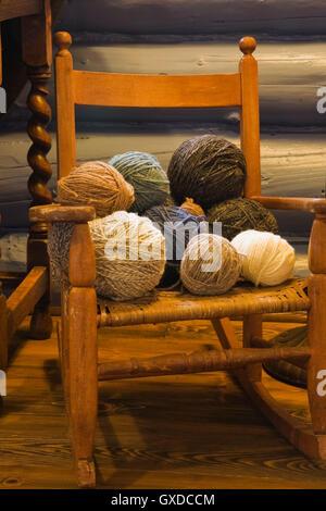 Wollknäuel auf kleine alte Holz Schaukelstuhl im Schlafzimmer des Landes Cottage Stil Wohn Blockhaus, Quebec, Kanada - Stockfoto