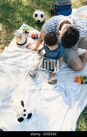 Draufsicht der junge Mann und Kind Sohn mit digital-Tablette auf der Picknickdecke in Pelham Bay Park, Bronx, New - Stockfoto