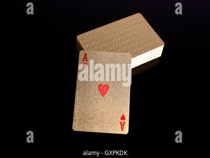 Goldene Spielkarten mit Ass an der Spitze auf schwarzem Hintergrund - Stockfoto