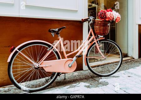 Vintage Rosa Fahrrad mit einem dekorativen Korb mit Blumen auf Straße In europäischen Stadt - Stockfoto